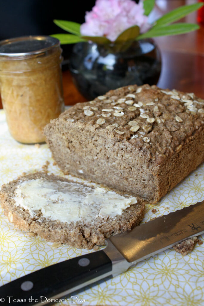 a single slice of oatmeal bread in fromt of the entire loaf with butter