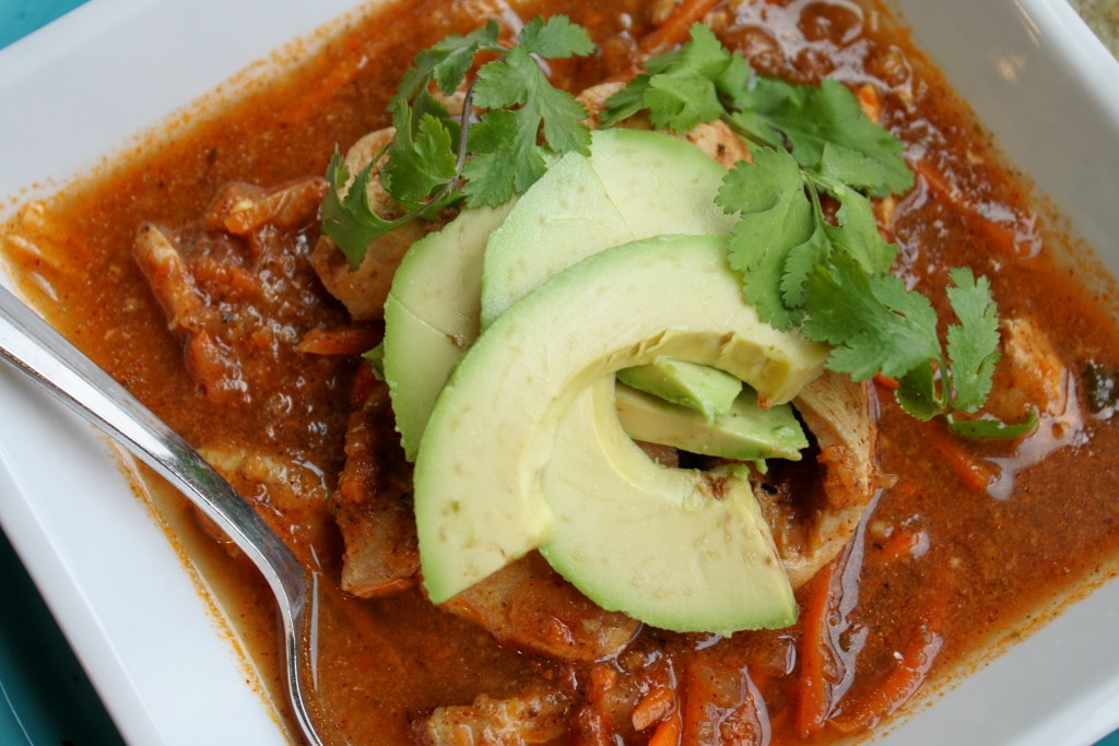 closeup overhead shot of a square white bowl filled with a mexican tomato broth soup garnished with fresh cilantro and avocado slices