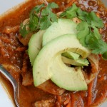 birdseye view of a white bowl filled with a savory mexican tomato broth topped with sliced avocado and cilantro