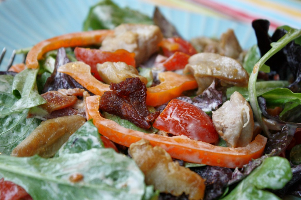 a up close view of a blt salad with a creamy mayo dressing, bacon, tomato, and crispy chicken thighs