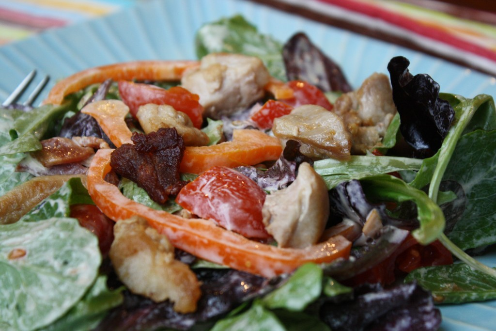close up of a blue plate with creamy coated salad greens with peppers, chicken, bacon, and tomatoes