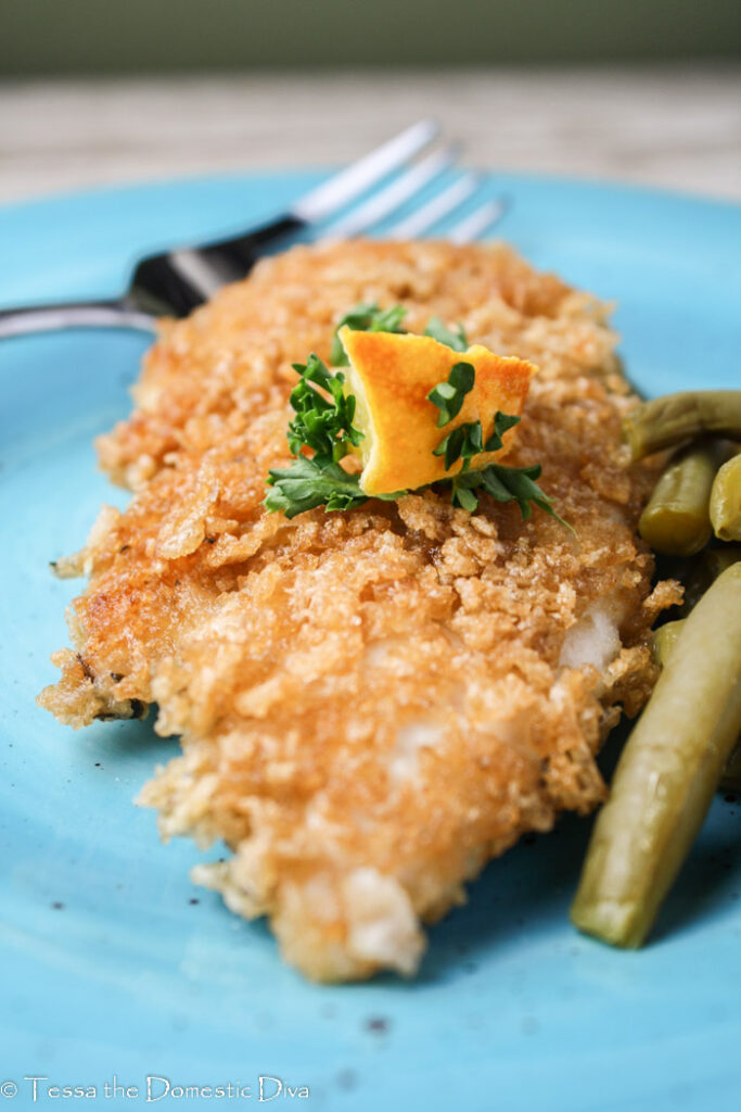gluten free panko crusted chicken breast with a wedge of lemon and fresh parsley on a blue plate