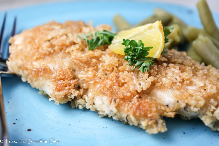 a gluten and egg free panko crusted chicken breast from eye level on a turquoise plate topped with a lemon wedge and chopped parsley
