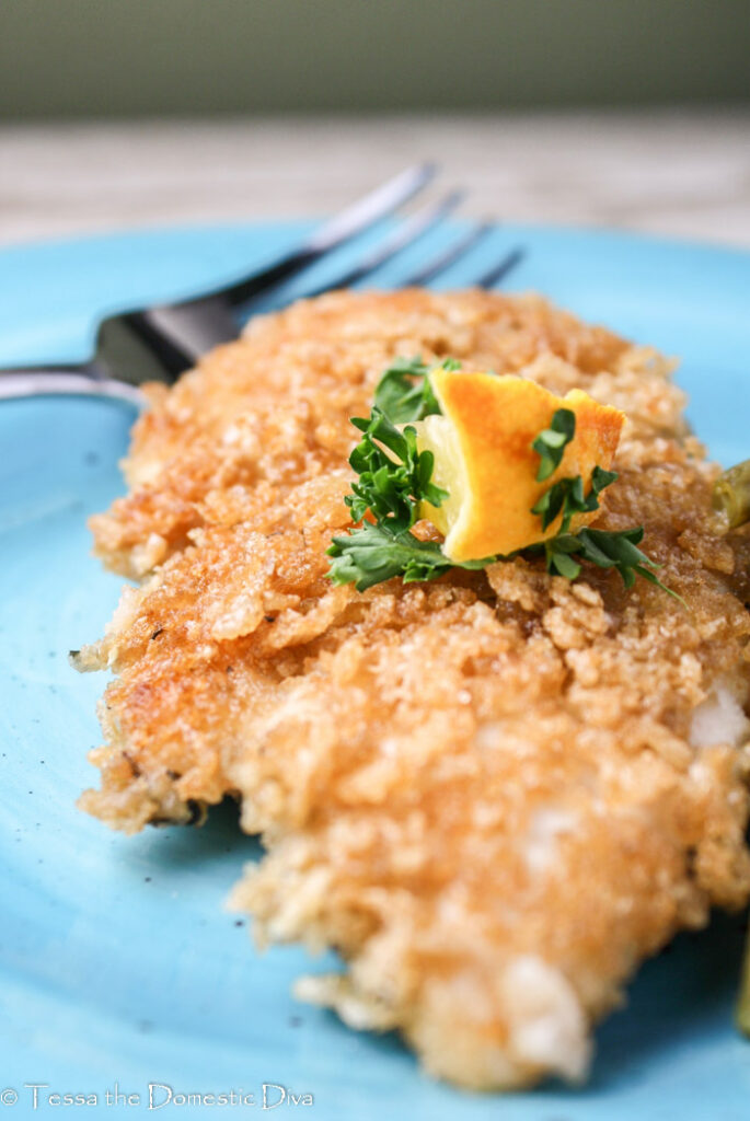 crispy coated chicken breast topped with lemon and parsley garnish