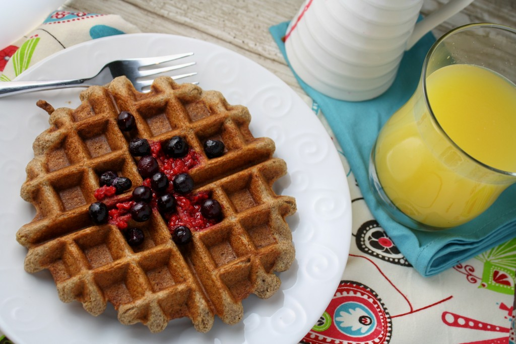 horizontal image of a golden brown waffle on a white plate topped with raspberry puree and blueberries with a side of orange juice