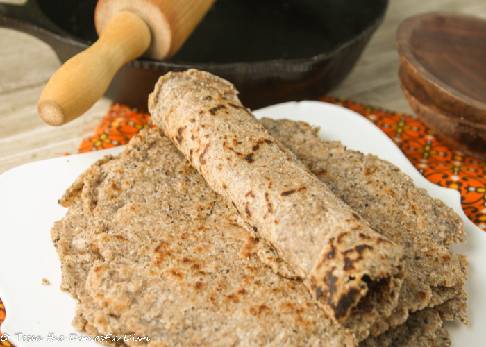a stack of gluten free tortillas withn idividual rolled tortilla placed on top and a rolling pin and cast iron skillet in background