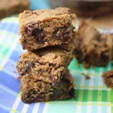 3 stacked sqaures of a sunbutter and chococalte blondie atop a blue and green plaid cloth