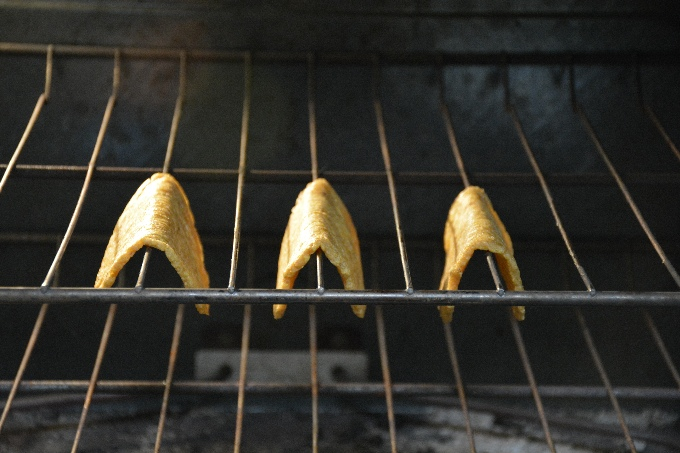 horizontal image of three whole 30 plantain taco shells draped over the oven racks crisping up