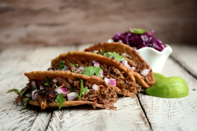 horizontal image of three crunchy plantain taco shells filled with pulled pork, purple cabbage, and cilantro arranged on a white washed board