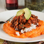 a bed of mashed sweet potatoes on a white plate with a topping of Cuban picadillo with ground beef