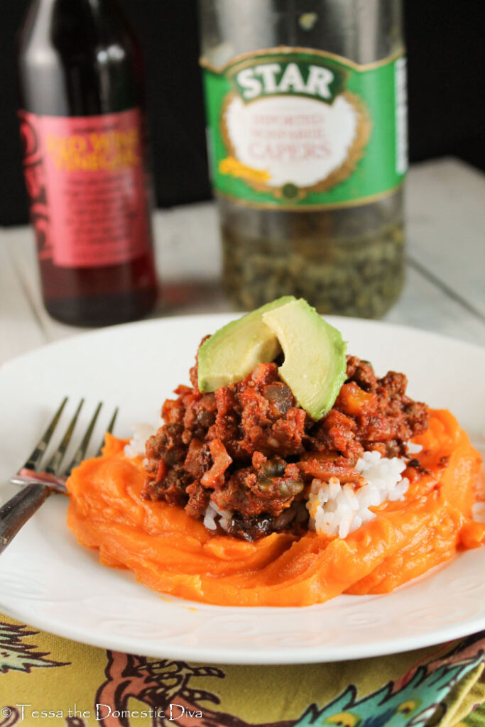 a white plate with Cuban picadillo on a bed of bright orange sweet potato mash with a jar of capers and red wine vinegar in the background