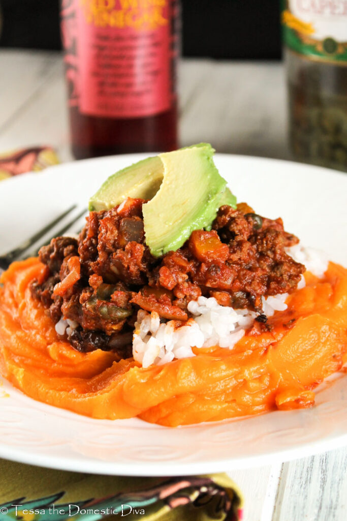 a white plate with garlic mashed sweet potato topped with Cuban picadillo and sliced avocado