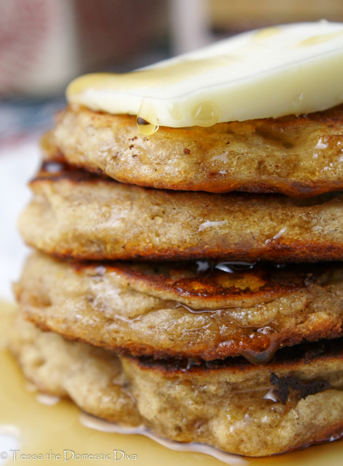 eye level close up of a stack of 4 wholegrain gluten free vegan pancakes with a pat of butter and maple syrup oozing down over the top