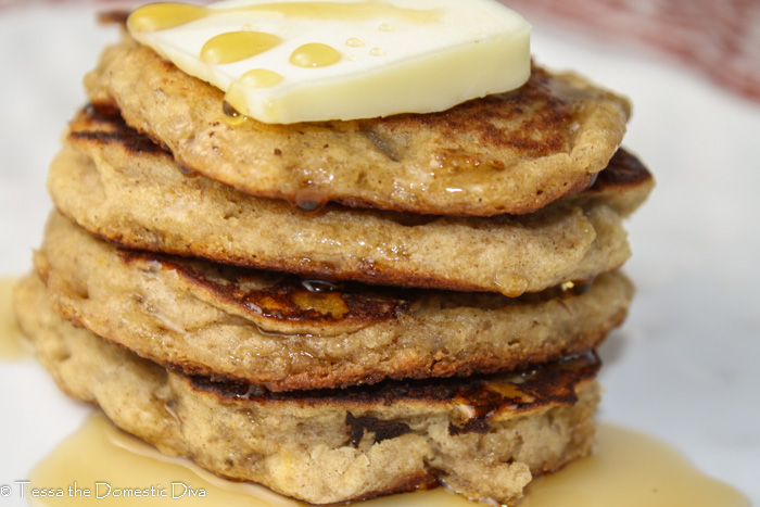 a stack of 4 pancakes with a pat of butter and maple syrup drizzle on a white plate