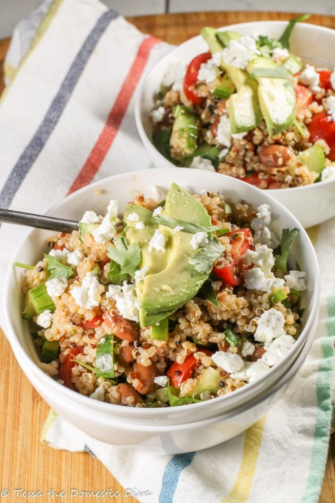 two white bowls filled with quinoa salad garnished with avocado, feta, and cilantro