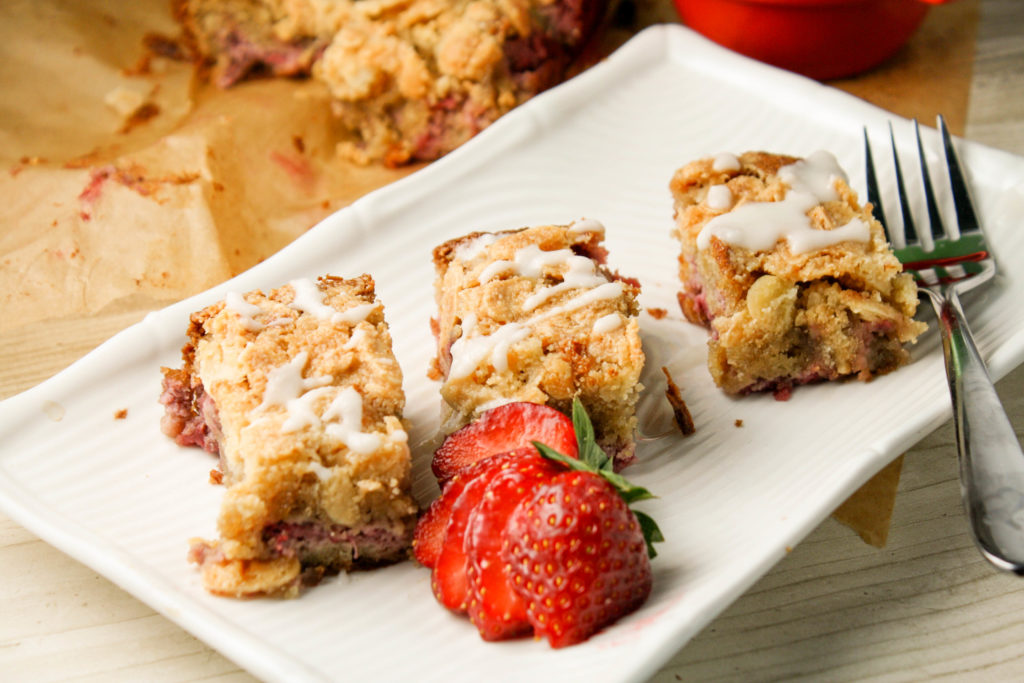 three rectangle shaped slices or a coffee cake studded with diced starwberries on a white plate with a fresh starwberry garnish and white drizzle