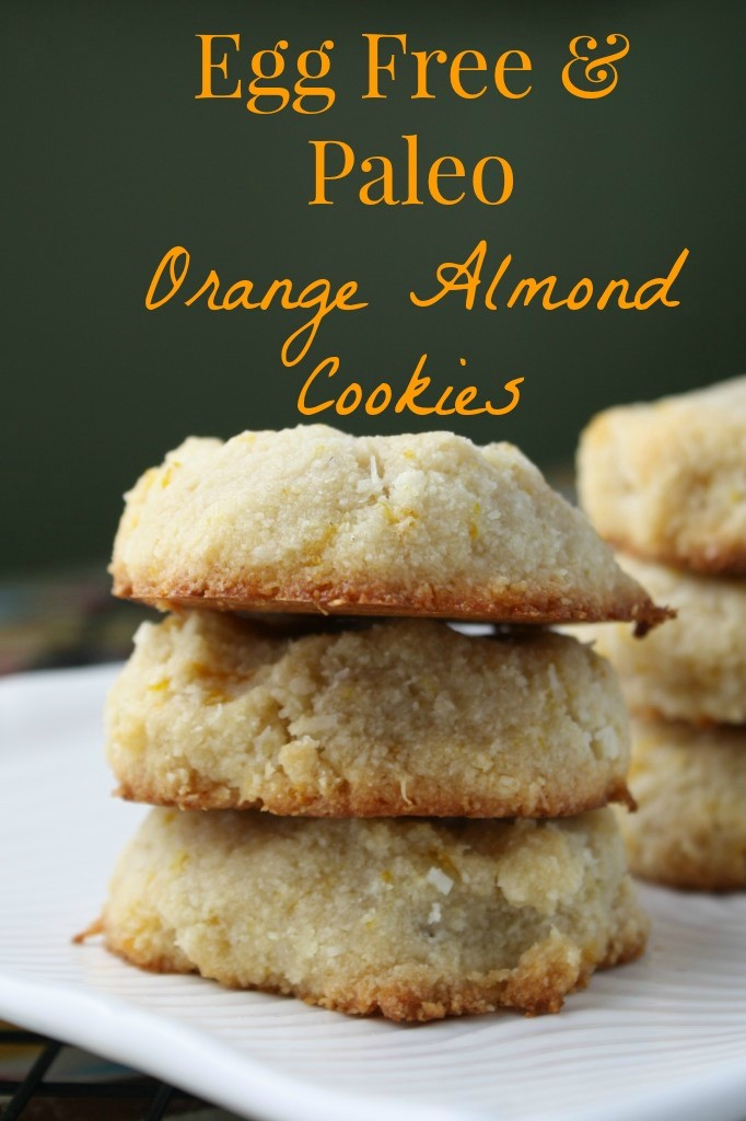 optimized for pinterest three stacked orange almond cookies with golden bottoms with a dark green backdrop