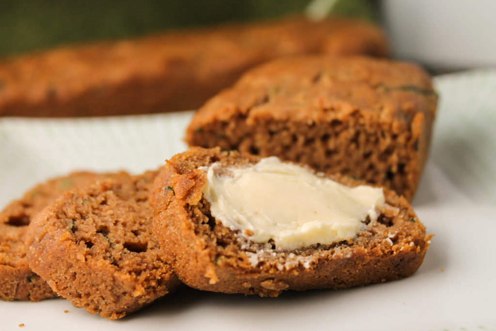 horizontal image of sliced gluten free began zucchini bread with a slathering of butter on a white plate at eye level
