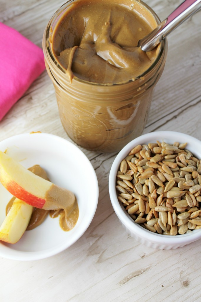 fresh homemade creamy sunflower seed butter in a mason jar with a white bowl of whole sunflower seeds and a sliced apples with a red skin