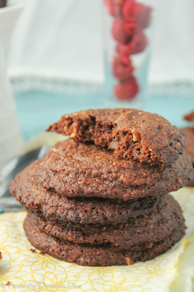 several stacked chocolate hazelnut cookies with a cup of red berries in the background