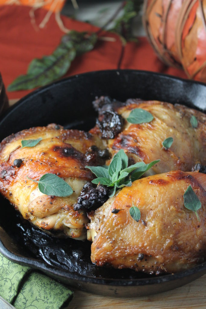 vertical image of a healthier low sugar chicken marbella in a cast iron pan with bits of prune and a fresh oregano garnish