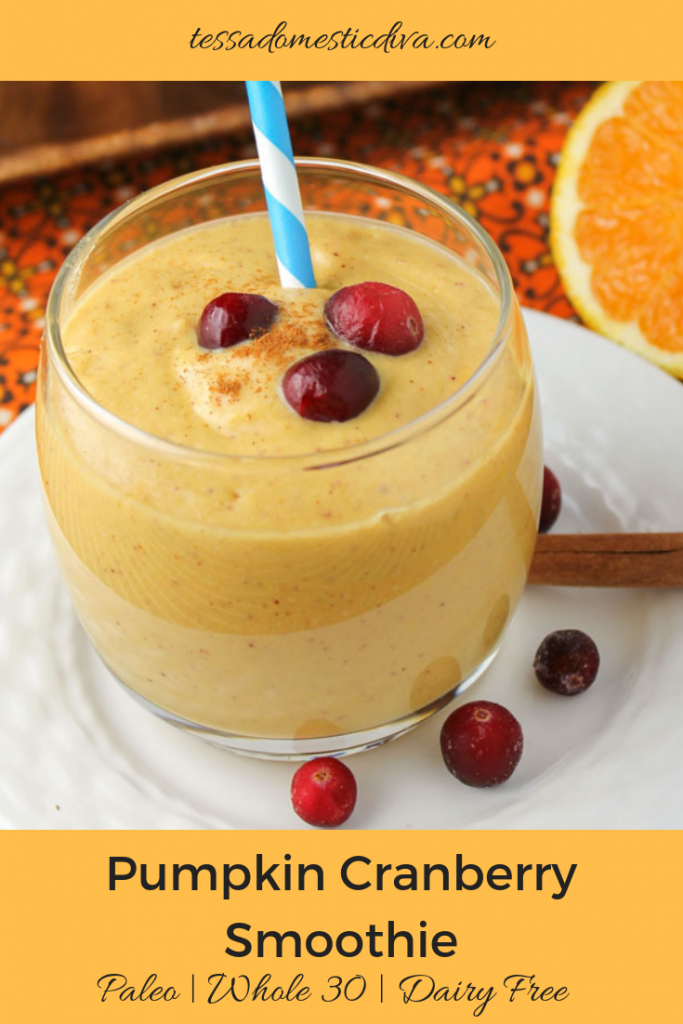 optimized for pinterest creamy pumpkin smoothies topped with fresh cranberries, cinnamon, and a wedge of a navel orange in a clear glass on a white plate