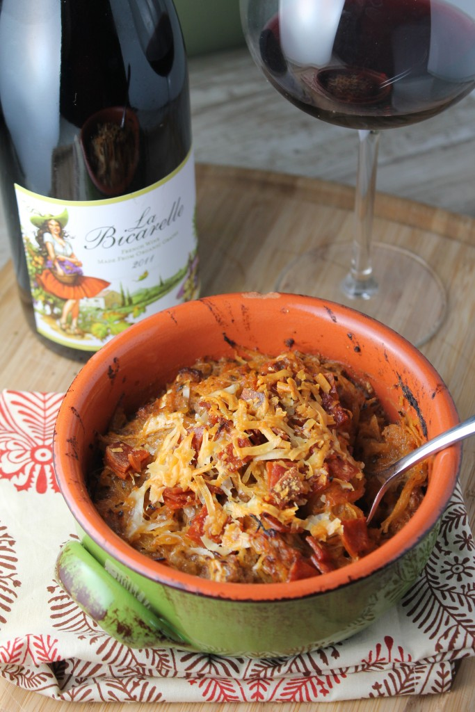 vertical image of keto pizza casserole in a green terracotta pottery bowl with a glass of red wine in the background