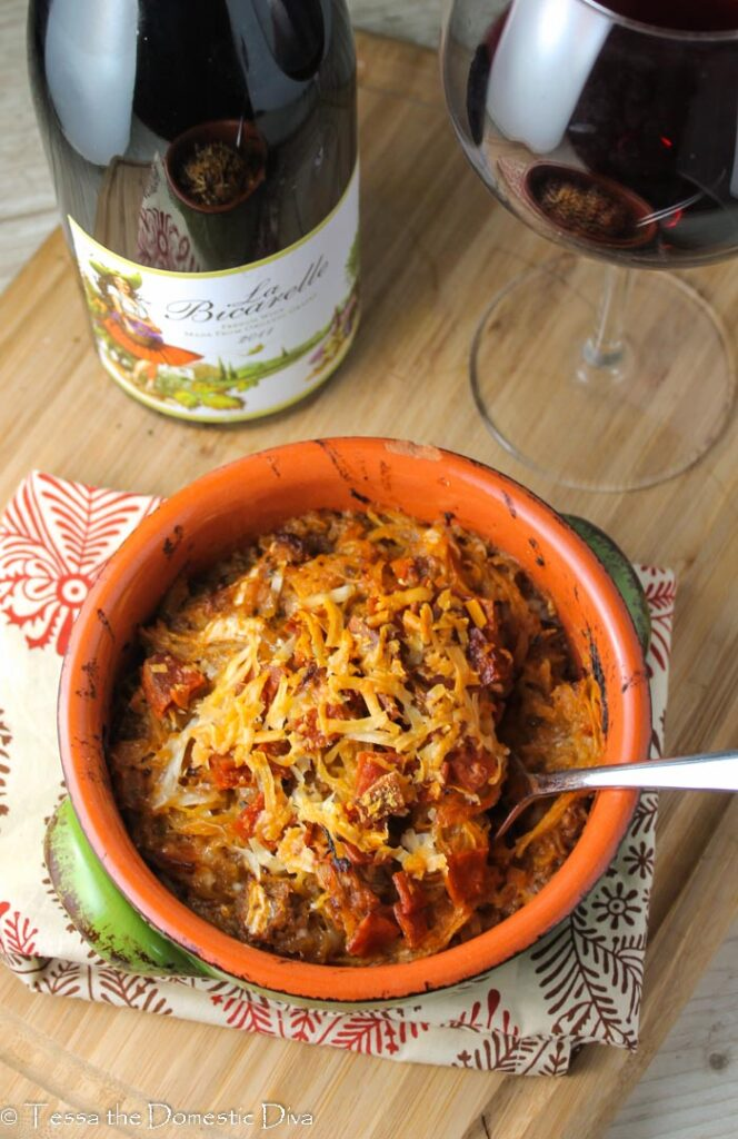 birds eye view of a green ceramic bowl filled with a spaghetti squash pizza casserole with a glass of red wine
