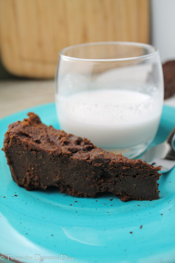 a slice of dense and fudgy gluten free vegan brownie on a blue plate with a glass of milk