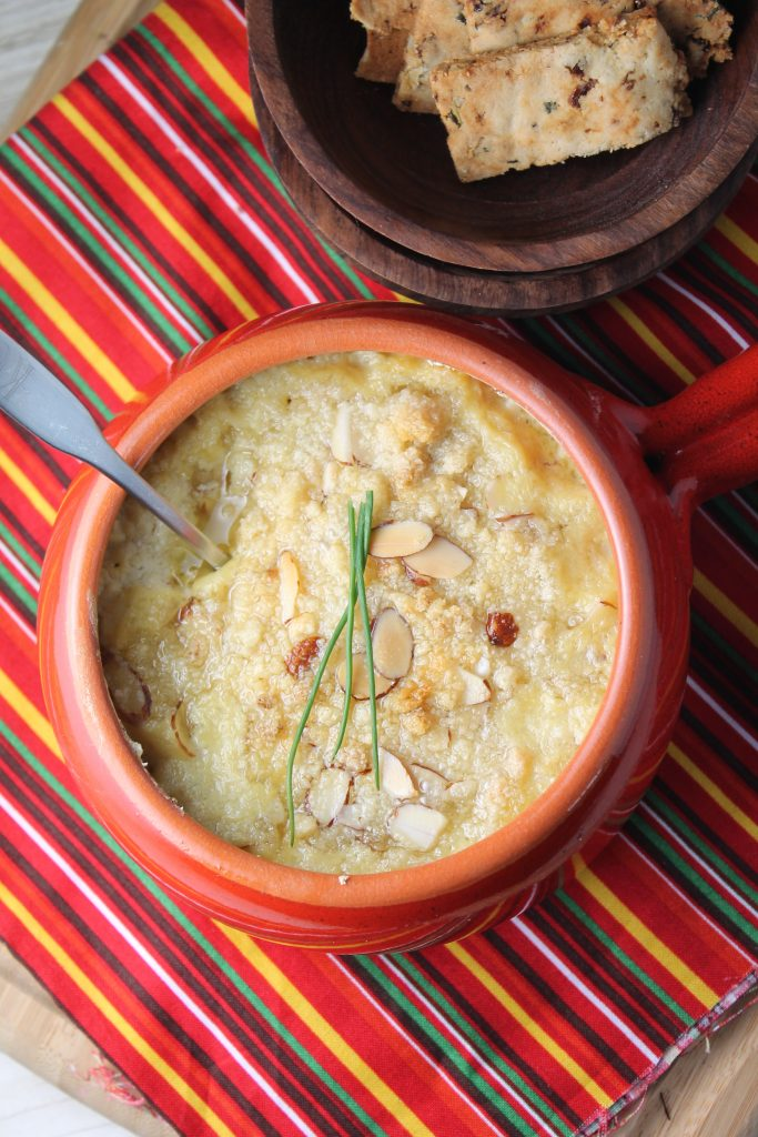 overhead look at a golden brown and crisped hot artichoke dip with an almond topping and homemade almond crackers in the background