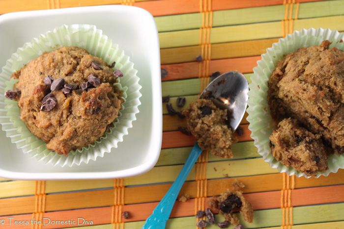 banana chocolate chip muffins in a small square bowl on a citrus colored wooden placemat.