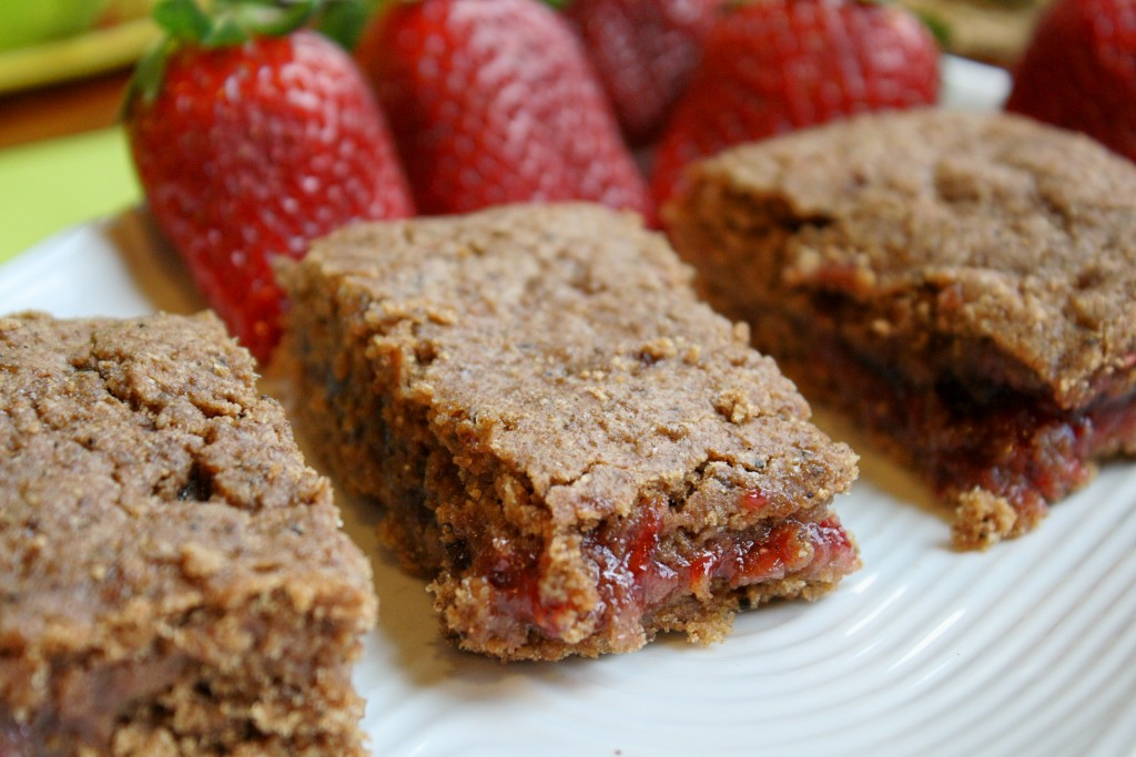 horizontal image of healthy homemade cereal bars with a strawberry filling on a white plate with fresh whole strawberries in the background