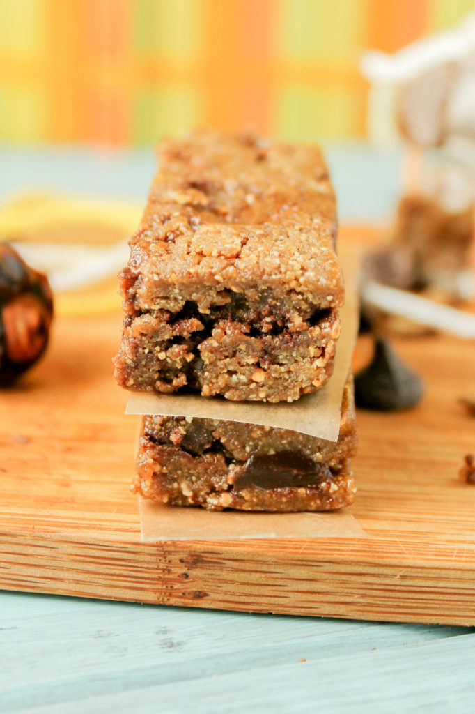 2 rectangular nut and date bars with chocolate chips separated by a piece of parchment on a bamboo cutting board at eye level
