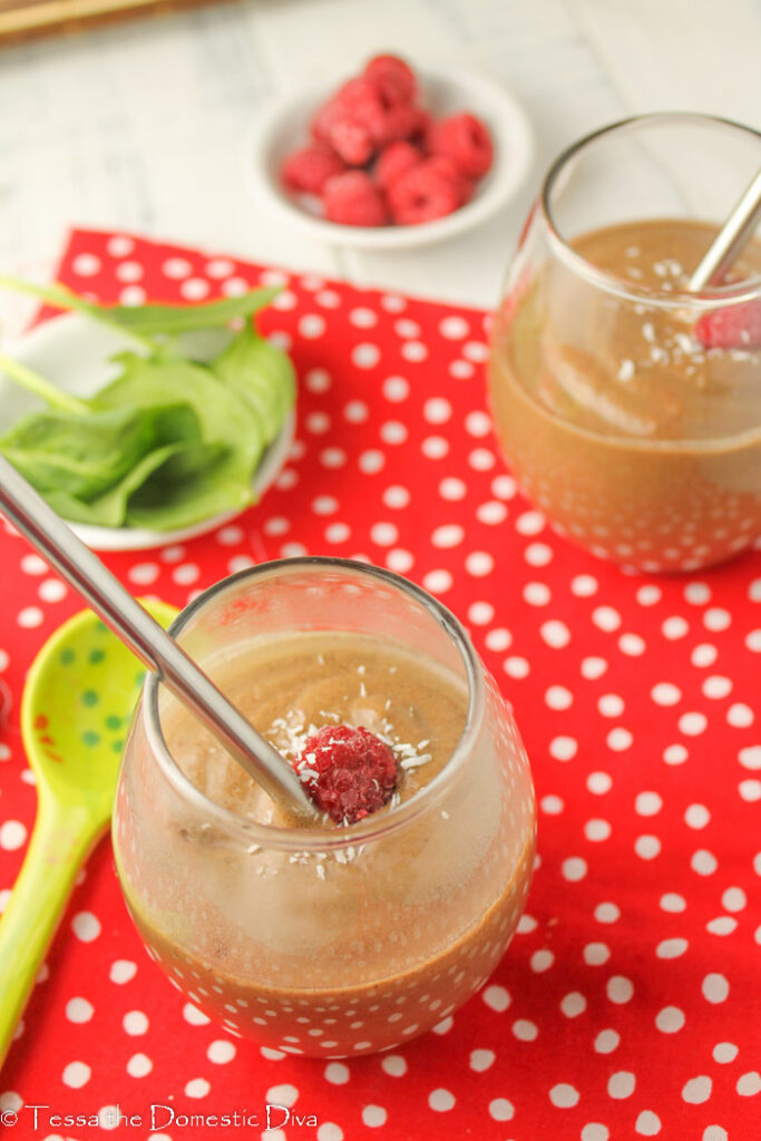two clear glasses filled with a creamy chocolate smoothie with avocado spinach and fresh raspberries