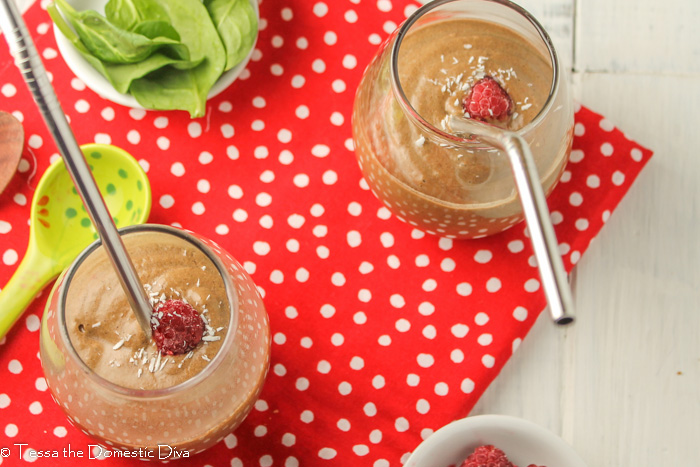 two glasses from above on a red cloth and filled with a chocolate raspberry smoothie