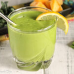 a clear class with a thick and creamy green smoothie with mango and lemon and coconut
