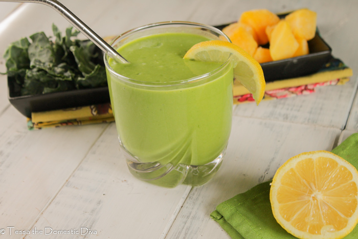 a glass of green smoothie with a reusable straw, a lemon slice, greens, and mango on a white wooden surface