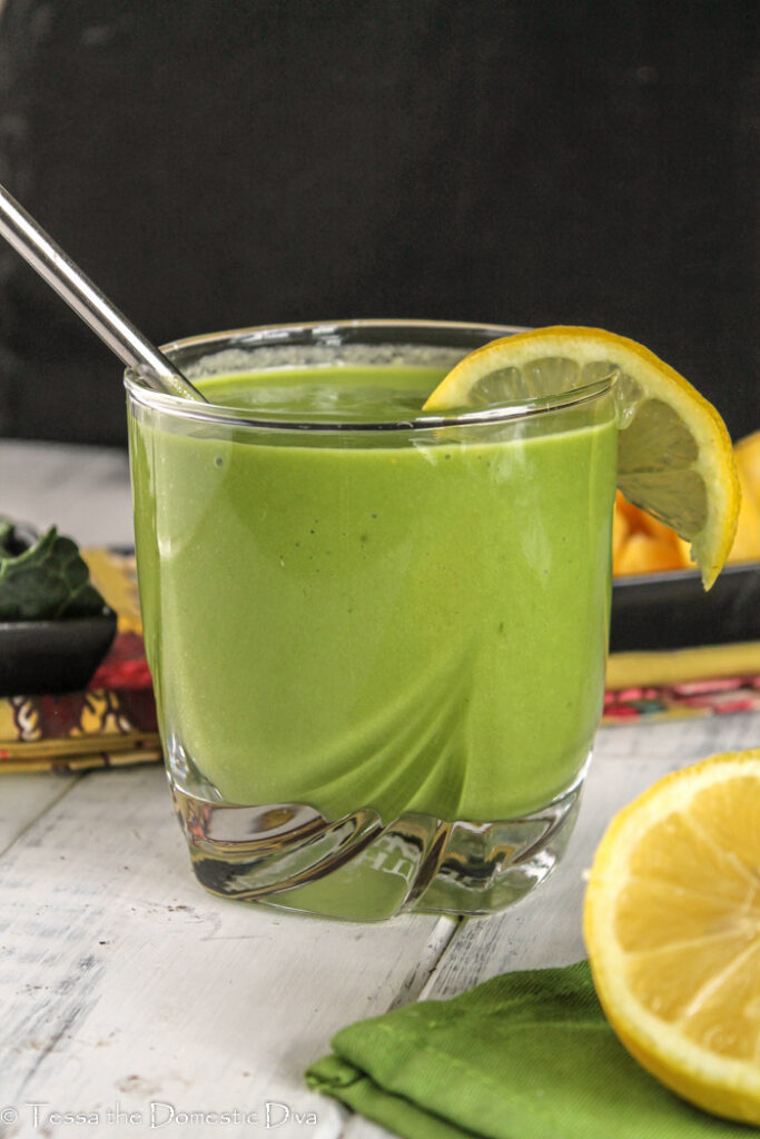 a clear glass with a stainless straw filled with a vibrant green smoothie with a slice of lemon on the glasses edge at eye level