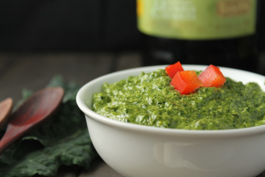 eye level white bowl filled with a vibrant green pesto sauce with olive oil, kale in background