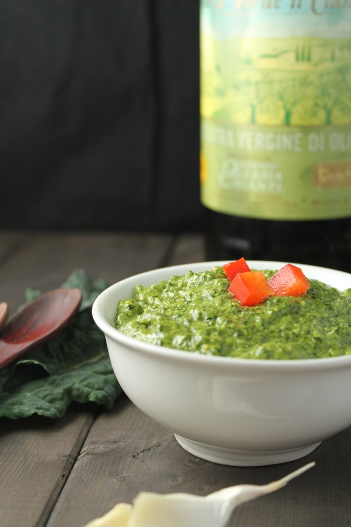 eye level image of a creamy bright green pesto with a cherry red pepper garnish on a dark wood surface