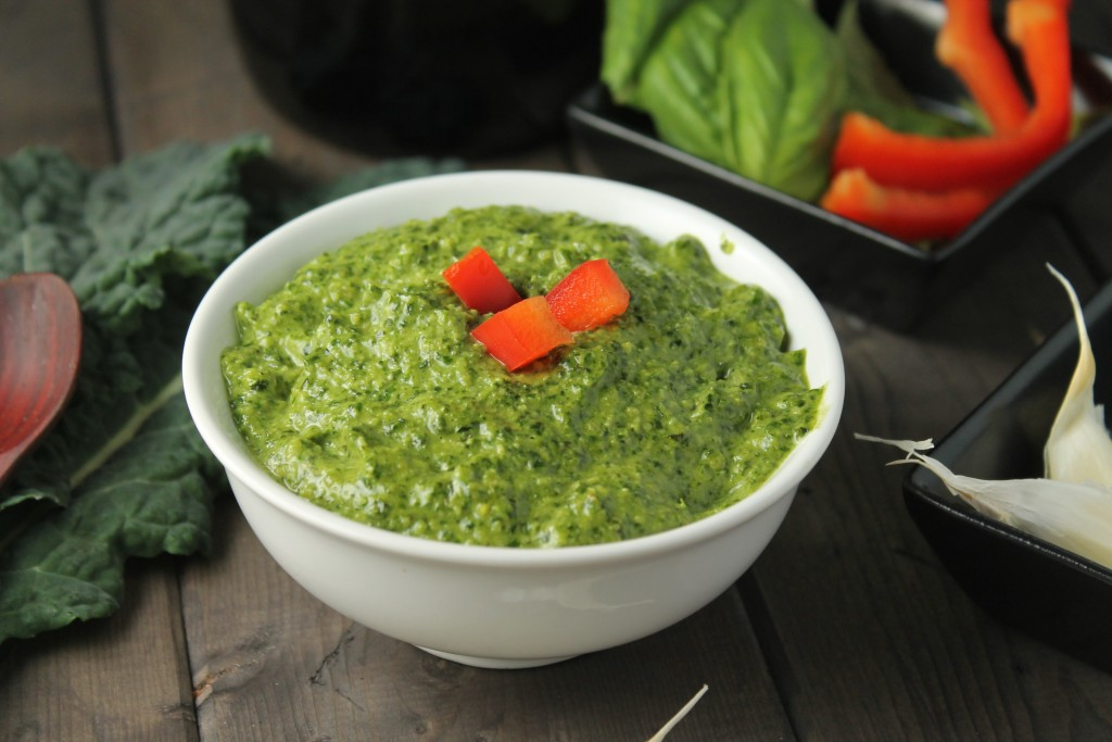 bright green pesto in a white bowl topped with diced red pepper on a dark wooden surface