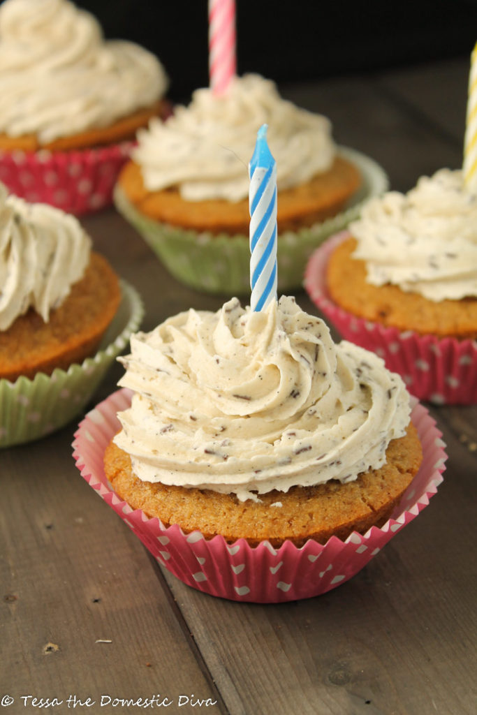 vanilla cupcakes arranged on a dark wooden surface with swirled vanilla frosting and a single birthday candle in each cupcake