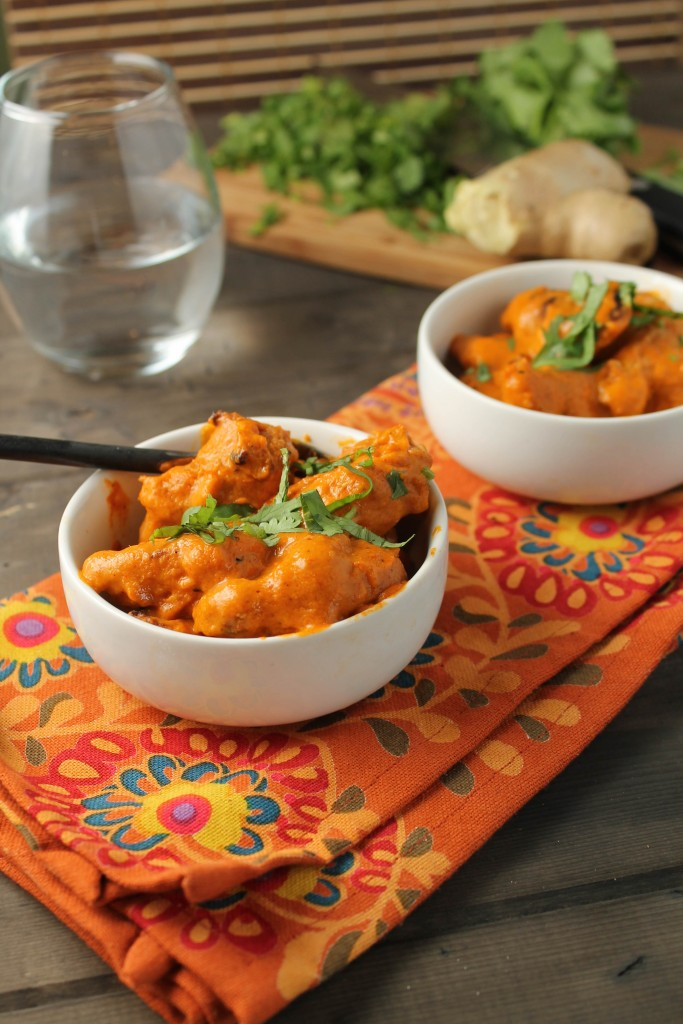 two white bowls filled with chicken tikka masala on an orange paisley cloth