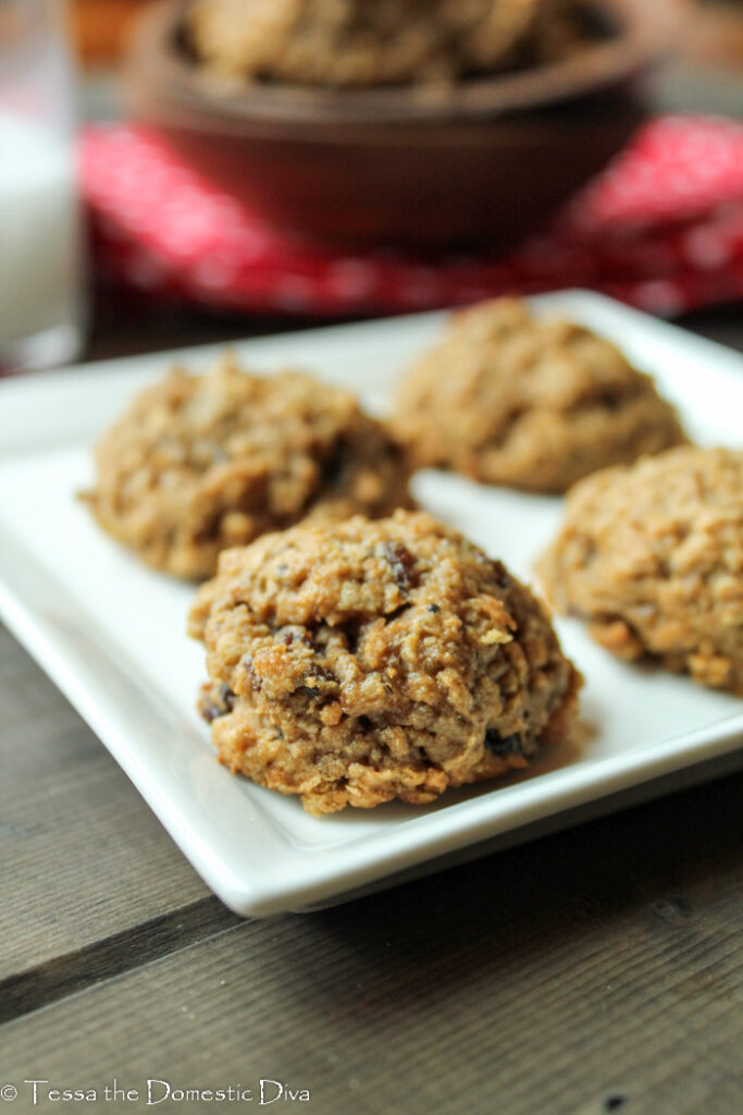 eye level image of 4 oatmeal cookies on a square white plate with raisins and a red cloth