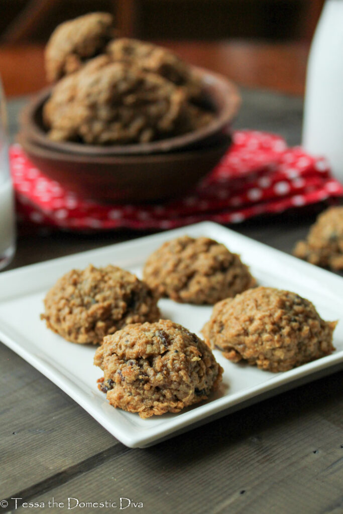 an arrangement of 4 oatmeal raisin cookies on a white plate with additional cookies stacked in a wooden bowl in the background