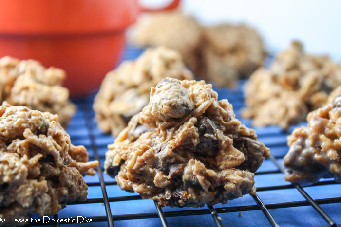 multiple chocolate chip oatmeal cookies on cooling rack atop a royal blue surface