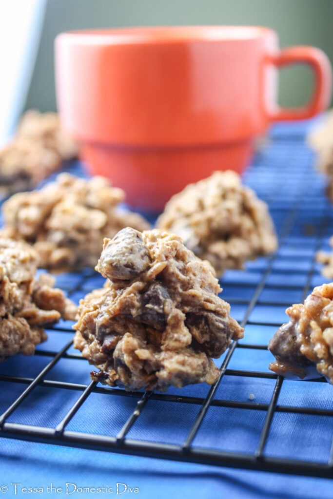oatmeal chocolate cookies arranged on a cooling rack with a red mug and royal blue linen