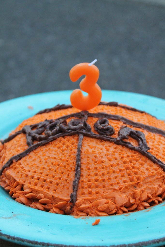 a basketball children's birthday cake with a number 3 candle on top