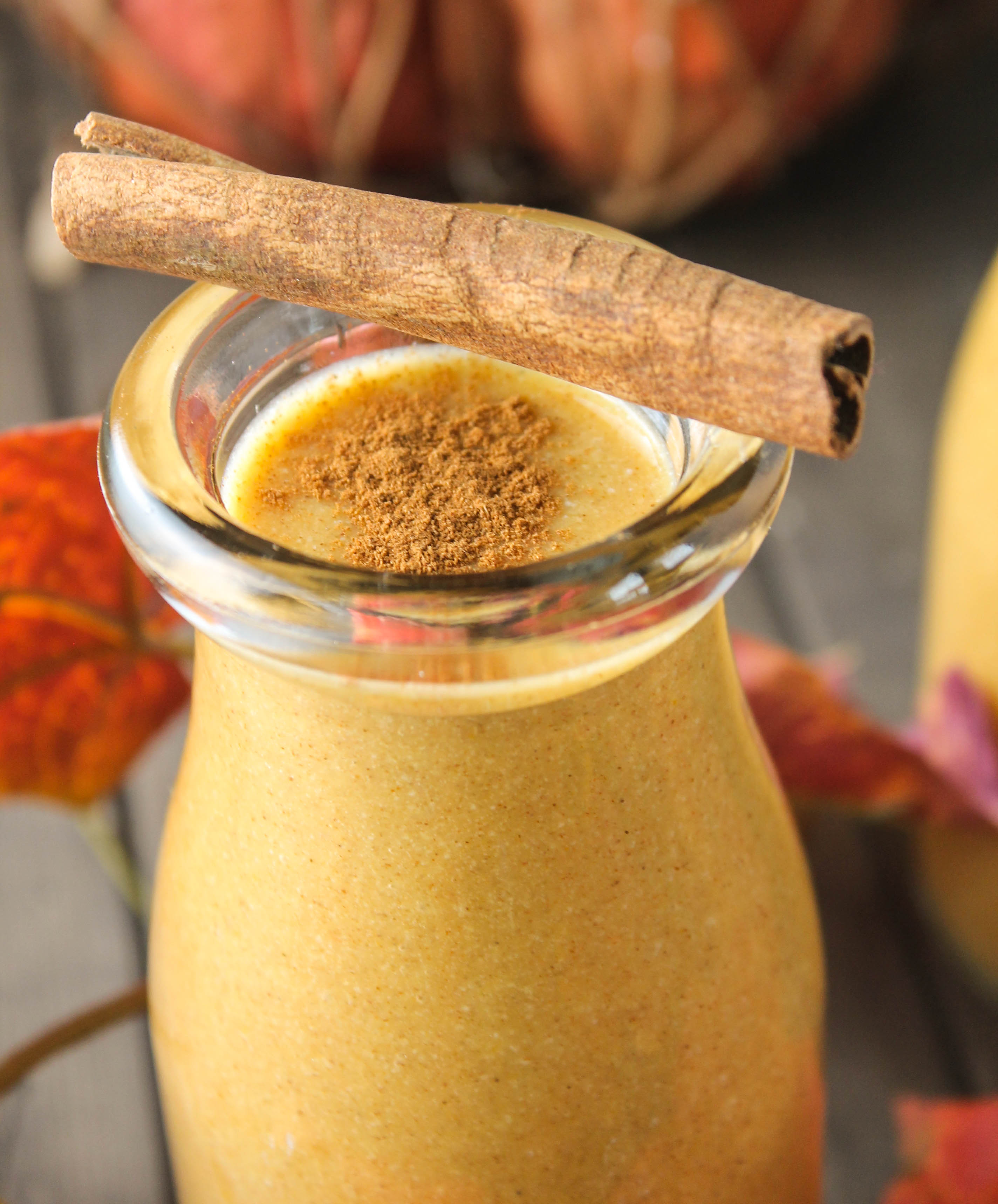 a close up of a clear glass filled with an orange colored pumpkin smoothie topped with a sprinkle to cinnamon and a cinnamon stick resting on the glass's edge