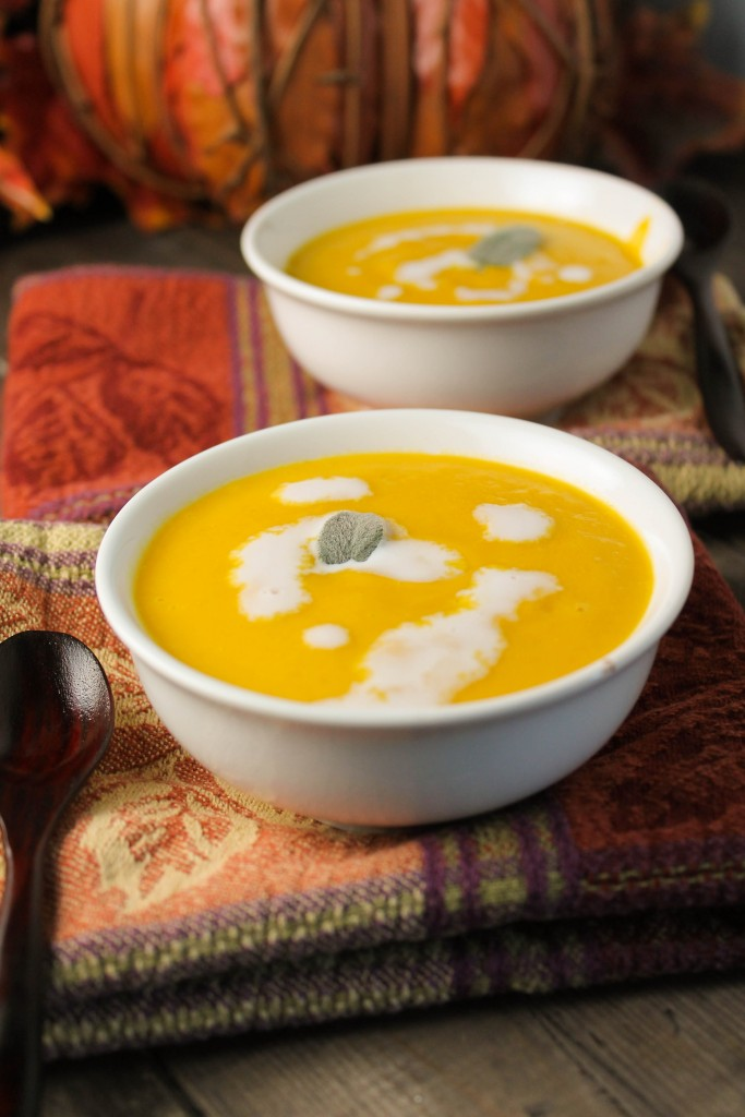 two white bowls on top of fall colored napkins filled with orange pumpkin soup and dollops of creams and a garnish of sage
